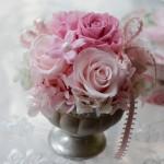 アンティーク調の花器に華やかなピンク系のアレンジ。 アクセントにミントグリーンの紫陽花が入っています。